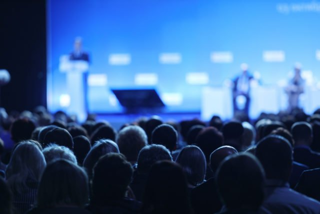 Presenter on Stage with audience in foreground