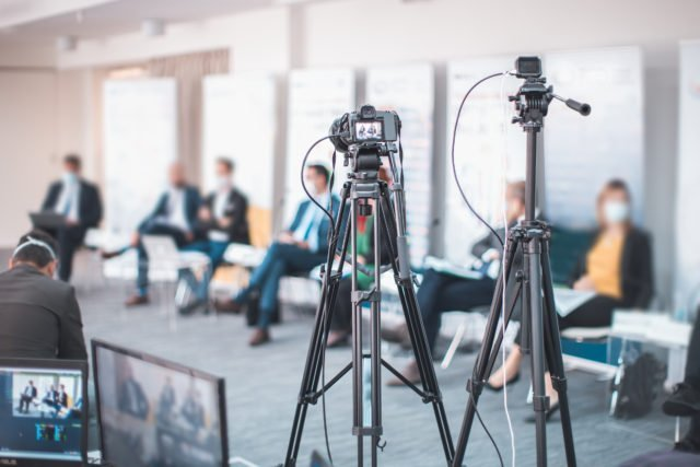 Steaming cameras, panel, and audience at Hybrid Meeting