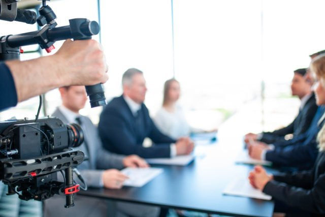 Videographer filming hybrid business meeting