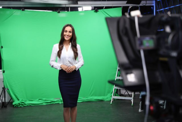 Female Presenter in front of green screen and video camera operator working in studio